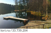 Morning at calm forest lake with frost on earth and wooden pier, cold autumn season. Sunlight from rising sun on the trees. Стоковое видео, видеограф Кекяляйнен Андрей / Фотобанк Лори