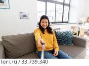 Купить «woman taking picture with selfie stick at home», фото № 33739340, снято 14 марта 2020 г. (c) Syda Productions / Фотобанк Лори