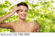 Купить «young woman with toner or cleanser and cotton pad», фото № 33740060, снято 30 ноября 2019 г. (c) Syda Productions / Фотобанк Лори