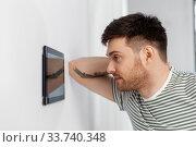 Купить «man looking at tablet computer at smart home», фото № 33740348, снято 21 марта 2020 г. (c) Syda Productions / Фотобанк Лори