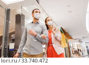 Купить «couple in medical masks with shopping bags in mall», фото № 33740472, снято 10 ноября 2014 г. (c) Syda Productions / Фотобанк Лори