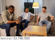 Купить «happy male friends talking at home at night», фото № 33740500, снято 28 декабря 2019 г. (c) Syda Productions / Фотобанк Лори