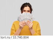 Купить «young woman covering her face with dollar money», фото № 33740804, снято 20 марта 2020 г. (c) Syda Productions / Фотобанк Лори