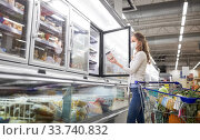Купить «woman in mask choosing ice cream at grocery store», фото № 33740832, снято 21 октября 2016 г. (c) Syda Productions / Фотобанк Лори