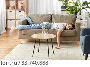 Купить «bored or lazy young woman lying on sofa at home», фото № 33740888, снято 15 апреля 2020 г. (c) Syda Productions / Фотобанк Лори