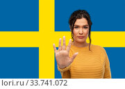 Купить «woman showing stop gesture over flag of sweden», фото № 33741072, снято 20 марта 2020 г. (c) Syda Productions / Фотобанк Лори