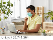 sick indian man in mask with laptop works at home. Стоковое фото, фотограф Syda Productions / Фотобанк Лори