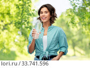 Купить «smiling woman drinking water from glass eco bottle», фото № 33741596, снято 18 апреля 2020 г. (c) Syda Productions / Фотобанк Лори