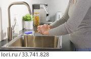 Купить «woman washing hands with liquid soap in kitchen», видеоролик № 33741828, снято 8 апреля 2020 г. (c) Syda Productions / Фотобанк Лори