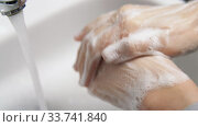 Купить «close up of woman washing hands with soap foam», видеоролик № 33741840, снято 4 апреля 2020 г. (c) Syda Productions / Фотобанк Лори