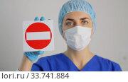Купить «doctor or nurse in face mask showing stop sign», видеоролик № 33741884, снято 8 апреля 2020 г. (c) Syda Productions / Фотобанк Лори