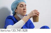 tired doctor or nurse drinking takeaway coffee. Стоковое видео, видеограф Syda Productions / Фотобанк Лори