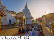 Утренняя  молитва в буддистском храме Kande Viharaya Temple. Берувала, Шри-Ланка (2020 год). Редакционное фото, фотограф Виктор Карасев / Фотобанк Лори