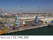 Купить «Four-link cargo loading cranes on dock with parked motor vehicles ready for shipping plus container loading cranes in background, Ashdod Port, Israel.», фото № 33744308, снято 4 октября 2019 г. (c) age Fotostock / Фотобанк Лори