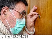 Купить «Covid-19 concept. Stay at home. Self-isolation to prevent the coronavirus pandemic. Senior man in protective green mask looks through the peephole.», фото № 33744788, снято 15 апреля 2020 г. (c) easy Fotostock / Фотобанк Лори