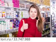 Купить «Stylish young female is touching her hair and satisfied», фото № 33747988, снято 22 марта 2018 г. (c) Яков Филимонов / Фотобанк Лори