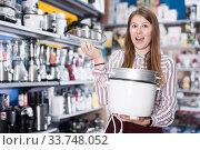 Happy girl shop assistant showing slow cooker in store. Стоковое фото, фотограф Яков Филимонов / Фотобанк Лори