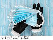 Купить «Medical man holds lot blue surgical face masks in black protective glove in hands. Concept quarantine, pandemic outbreak, hygiene», фото № 33748328, снято 8 мая 2020 г. (c) А. А. Пирагис / Фотобанк Лори