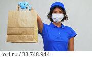 Купить «delivery woman in mask holding paper bag with food», видеоролик № 33748944, снято 9 апреля 2020 г. (c) Syda Productions / Фотобанк Лори