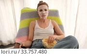 Купить «Concentrated natural blonde haired woman in sheet mask watching tv while eating popcorn in bright room», видеоролик № 33757480, снято 13 мая 2020 г. (c) Ekaterina Demidova / Фотобанк Лори