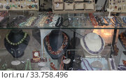 Купить «Colorful necklaces made from different precious stones for sale in jewelry store», видеоролик № 33758496, снято 31 октября 2019 г. (c) Яков Филимонов / Фотобанк Лори