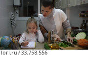 Little girl writing school lesson during mother cooking at kitchen. Стоковое видео, видеограф Яков Филимонов / Фотобанк Лори