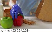 Купить «woman in gloves taking food from paper bag at home», видеоролик № 33759204, снято 3 мая 2020 г. (c) Syda Productions / Фотобанк Лори