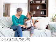 Купить «Senior Caucasian woman watching a family album at home with her granddaughter», фото № 33759340, снято 24 января 2020 г. (c) Wavebreak Media / Фотобанк Лори