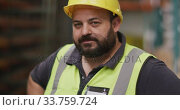 Caucasian male factory worker at a factory  wearing a high vis vest and a hard hat standing. Стоковое видео, агентство Wavebreak Media / Фотобанк Лори