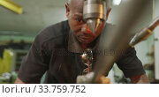 Купить «African American male factory worker at a factory standing at a workbench and operating machinery», видеоролик № 33759752, снято 23 ноября 2019 г. (c) Wavebreak Media / Фотобанк Лори