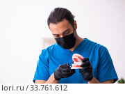 Купить «Young male dentist working in the clinic», фото № 33761612, снято 1 февраля 2020 г. (c) Elnur / Фотобанк Лори