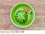 Small ripe cut watermelon and its slice on a green plate on a wooden tabletop. Стоковое фото, фотограф Евгений Харитонов / Фотобанк Лори
