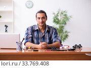 Купить «Young male technician repairing mobile phone», фото № 33769408, снято 6 сентября 2019 г. (c) Elnur / Фотобанк Лори