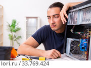 Young man repairing computer at home. Стоковое фото, фотограф Elnur / Фотобанк Лори
