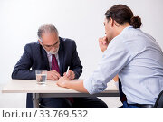 Old businessman meeting with advocate in pre-trial detention. Стоковое фото, фотограф Elnur / Фотобанк Лори
