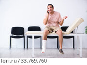 Купить «Young injured man waiting for his turn in hospital hall», фото № 33769760, снято 3 мая 2019 г. (c) Elnur / Фотобанк Лори