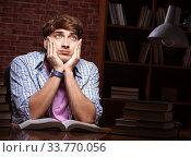 Купить «Young handsome student preparing for exams at night», фото № 33770056, снято 28 августа 2018 г. (c) Elnur / Фотобанк Лори