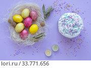 Купить «Easter eggs in the nest, cake, candles on a purple background», фото № 33771656, снято 12 апреля 2020 г. (c) Иванов Алексей / Фотобанк Лори