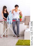 Купить «Young woman doing ironing for her husband», фото № 33771696, снято 27 июня 2018 г. (c) Elnur / Фотобанк Лори