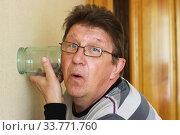 Мужчина при помощи банки подслушивает соседей. Стоковое фото, фотограф Евгений Будюкин / Фотобанк Лори