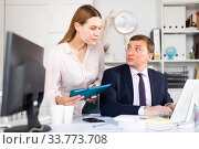 Head gives task to assistant at office at table. Стоковое фото, фотограф Яков Филимонов / Фотобанк Лори