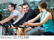 Купить «Adults riding stationary bicycles», фото № 33773840, снято 2 июля 2020 г. (c) Яков Филимонов / Фотобанк Лори