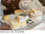 Купить «The waiter holds a plate with the Normandy cheeses», фото № 33773916, снято 19 мая 2019 г. (c) Ирина Аринина / Фотобанк Лори