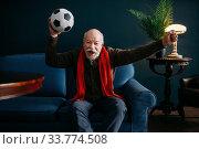 Купить «Elderly man with red scarf and ball, football fan», фото № 33774508, снято 7 февраля 2020 г. (c) Tryapitsyn Sergiy / Фотобанк Лори