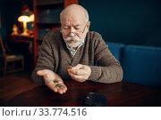Купить «Pour elderly man holds coins», фото № 33774516, снято 7 февраля 2020 г. (c) Tryapitsyn Sergiy / Фотобанк Лори