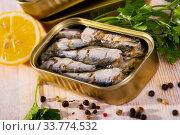 Tin can with smoked sprats, sardines, closeup. Стоковое фото, фотограф Яков Филимонов / Фотобанк Лори