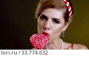 Купить «Woman retro style lick lollipop confection portrait», видеоролик № 33774632, снято 29 декабря 2019 г. (c) Gennadiy Poznyakov / Фотобанк Лори
