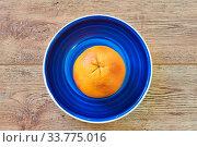 Rosy yellow grapefruit on a bright blue plate on a wooden tabletop. Стоковое фото, фотограф Евгений Харитонов / Фотобанк Лори