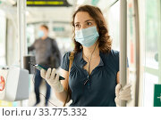 Modern girl in protective medical mask and gloves traveling in tram and using mobile phone. Стоковое фото, фотограф Яков Филимонов / Фотобанк Лори