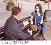 Купить «Emotional couple in protective medical masks against coronavirus communicate sittig on bench», фото № 33775344, снято 5 июля 2020 г. (c) Яков Филимонов / Фотобанк Лори